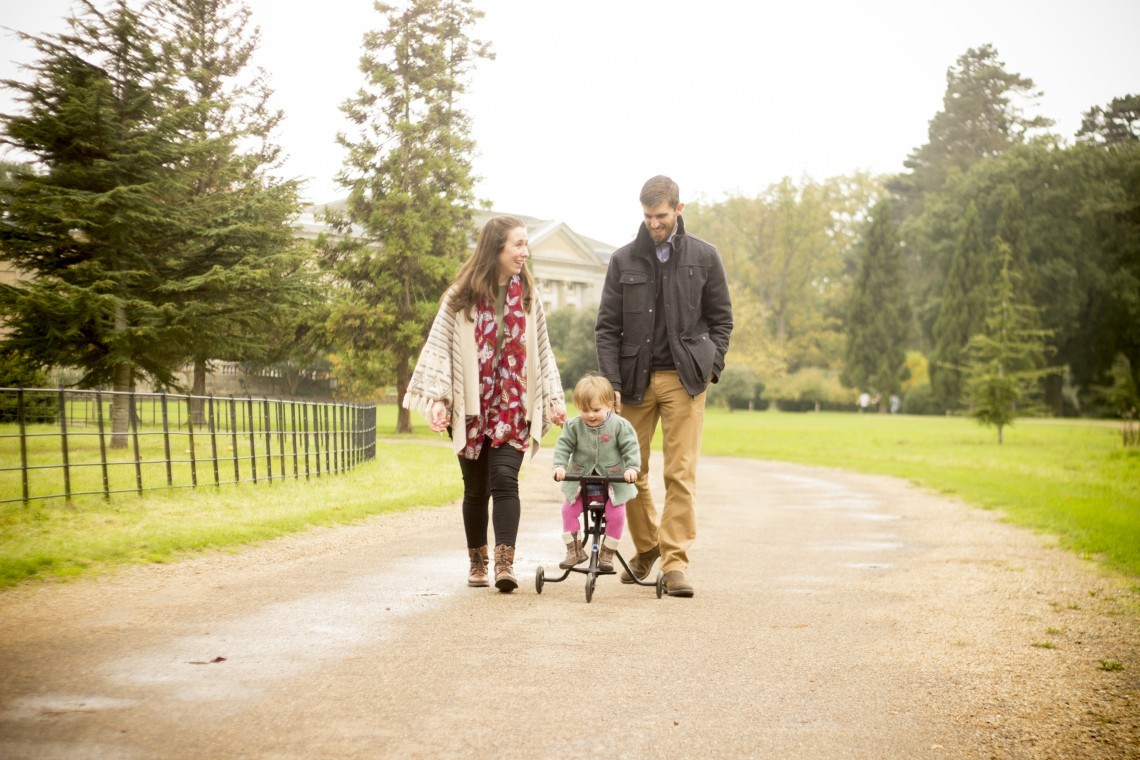 A couple walks while their toddler pedals a tricycle on The Ickworth hotel grounds.