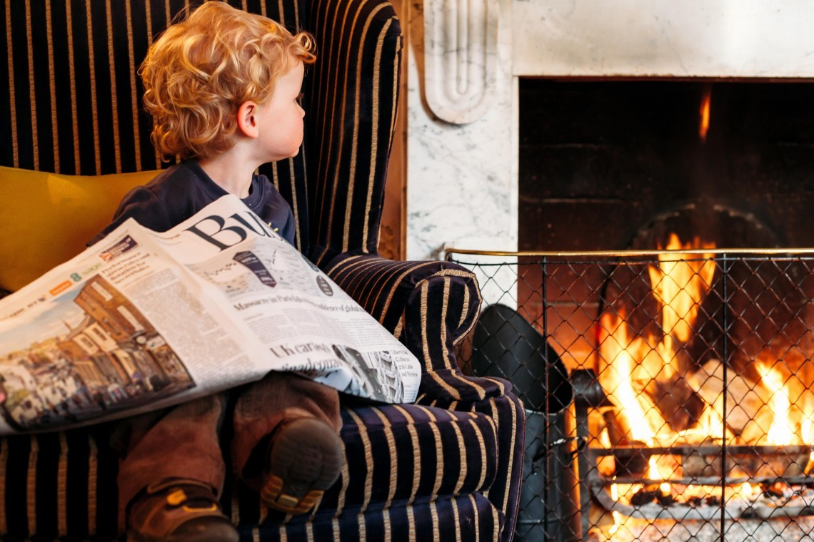 A young guest at a luxury family hotel sits by the fire