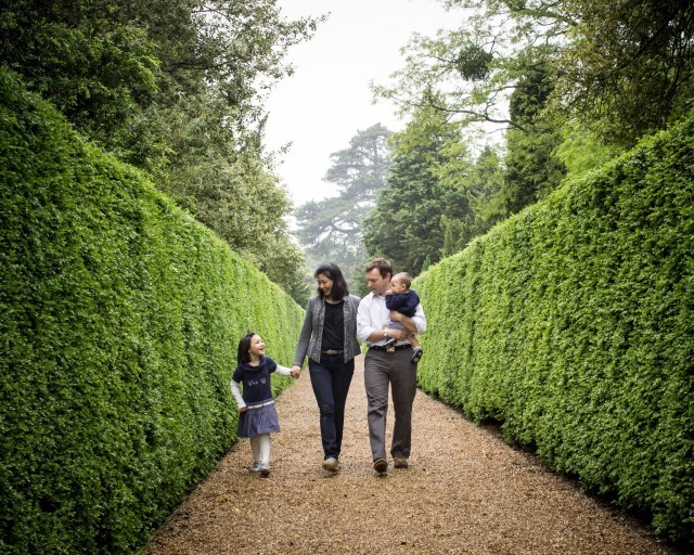 A family walk down a hedge-lined path at The Ickworth luxury hotel in Suffolk