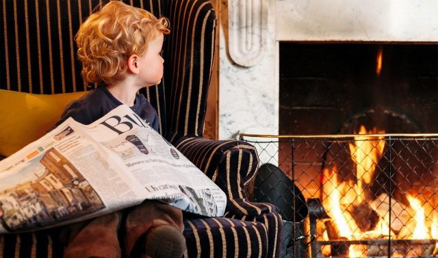 A young guest sits by the fire with a newspaper at a luxury family hotel