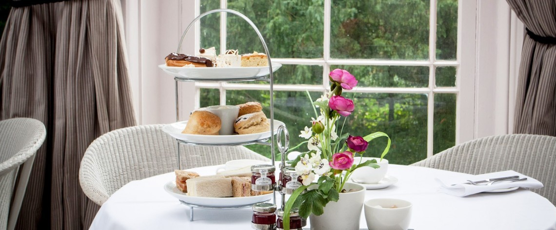 A three-tier afternoon tea on a table, with cakes, scones, sandwiches and preserves.