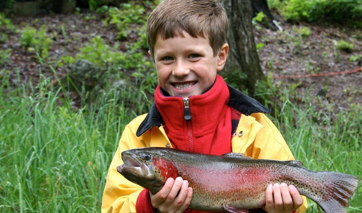 Boy with a trout at Larkwood Fishery in Suffolk