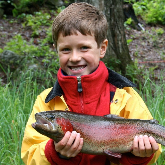 Boy holding his catch after trout fishing in Suffolk
